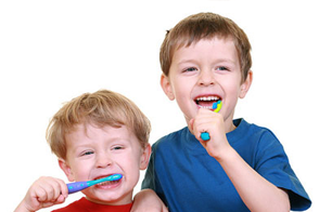 Children with toothbrushes in their mouths